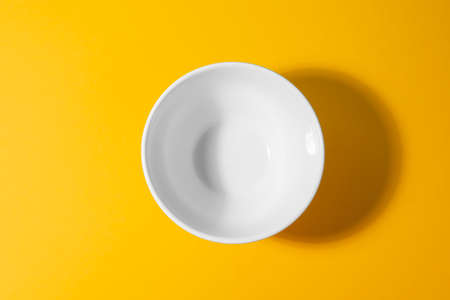 Top view on a white deep bowl on yellow background.