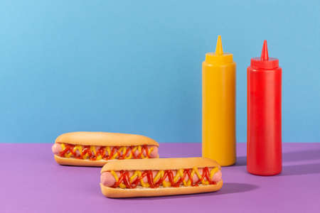 Two juicy hotdogs and squeeze bottles of mustard and ketchup