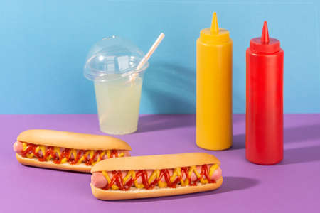 Two hotdogs, a cup of lemonade and squeeze bottles of mustard and ketchup