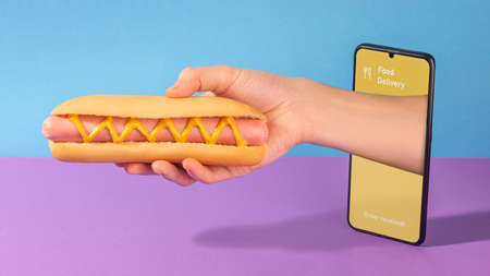 Hand giving a fresh hotdog out of a phone