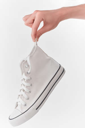 Hand holding a clean white canvas sneaker