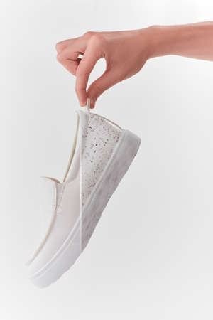 Hand holding a white leather slip-on shoe Reklamní fotografie