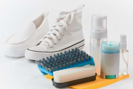 Leather and canvas shoes and cleaning kit on white background