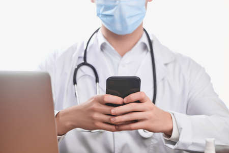Doctor using a cell phone to communicate with colleagues or patients Reklamní fotografie