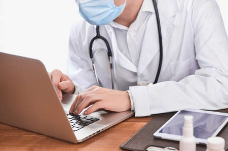 Physician typing on a laptop, giving an online consultation to a patient