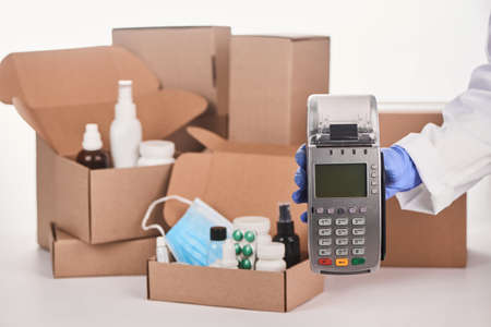 Pharmacists hand holding a POS terminal in front of boxes with medications
