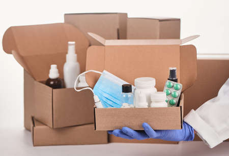 Pharmacists hand in glove holding a box with medicines and face mask Stock fotó