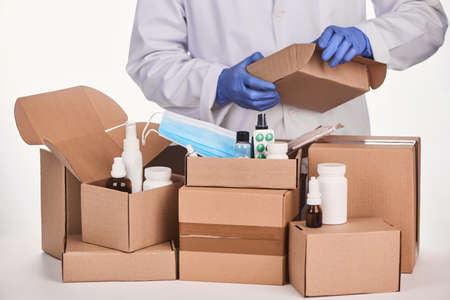 Pharmacist packing ordered medications and supplies into cardboard boxes