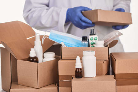 Various medicines being packed into cardboard boxes by a pharmacist
