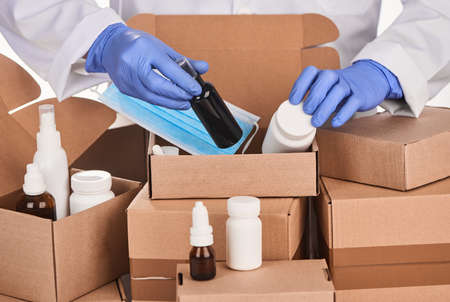 Pharmacist putting medicines into cardboard boxes for delivery
