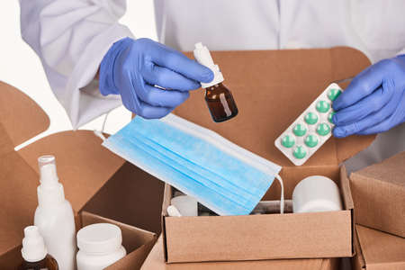 Doctor packing prescription medications and supplies for patients