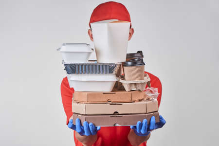 Delivery man holding a huge pile of various packed food
