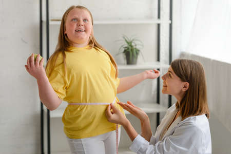 Girls waist being measured by a nutritionist