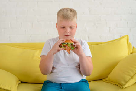 Obese boy eating a hamburger, sitting on a yellow couch