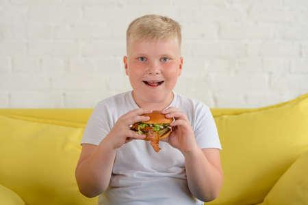 Happy boy eating a big hamburger, studio portrait