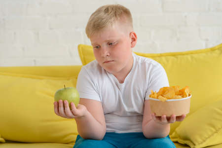 Sad fat boy looking at an apple and holding a cup of chips in another hand