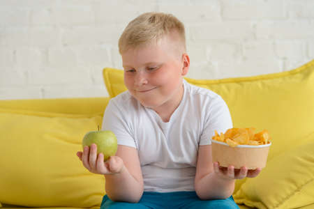 Happy fat boy looking at an apple and holding a cup of chips