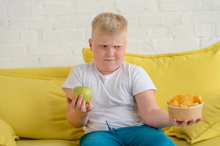 Boy holding apple and chips, and cant decide what to eat