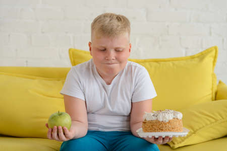 Confused boy choosing between an apple and a cake. Fruits or sweets