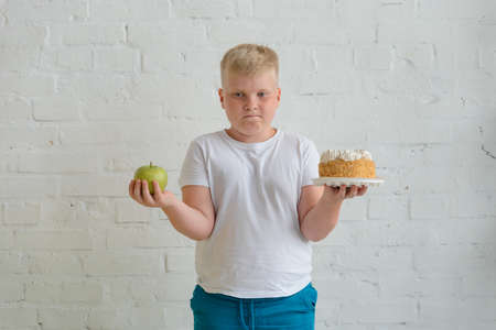 Obese boy choosing between foods. Apple or cake