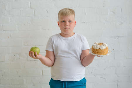 Unhappy overweight boy and food. Child holding an apple and a cake Stock fotó