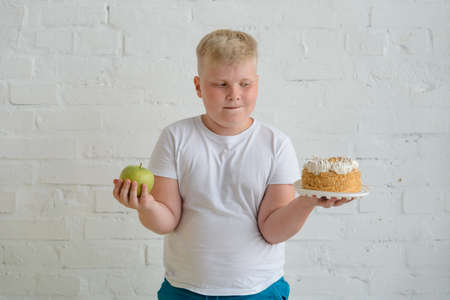 Obese boy holding an apple and a cake