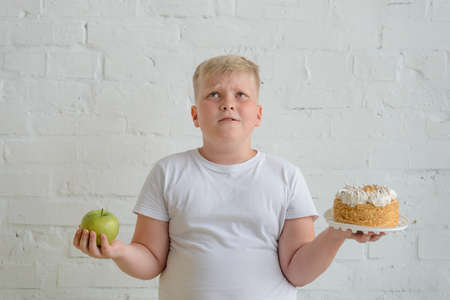 Crying fat boy choosing between an apple and a cake
