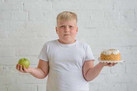 Boy choosing between apple and cake, studio portrait on white