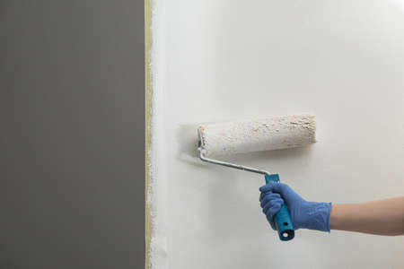 Handyman painting the gray wall white with a roller and masking tape Stock fotó