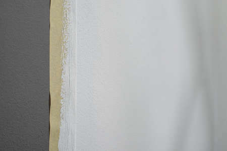 Part of gray wall painted white with masking tape Stock fotó