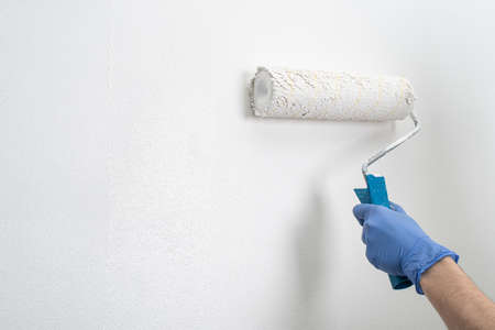 Hand applying a second layer of white paint with a roller onto the wall Stock fotó