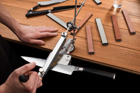 Man sharpening a Japanese knife with Damascus steel using a manual machine Stock fotó