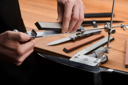 Close-up on hands inserting a whetstone into a manual sharpener machine. Fine and precise sharpening for a Japanese knife.