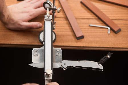 Man using a manual machine to sharpen a pocket knife