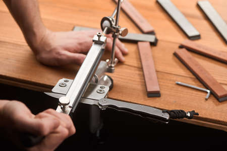 Close-up on mans hands using a manual machine to sharpen a folding knife