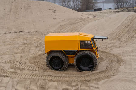 People driving an all-terrain vehicle, leaving twisted marks in the sand Stock fotó