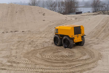 Yellow all-terrain vehicle driving and leaving twisted marks in the sand