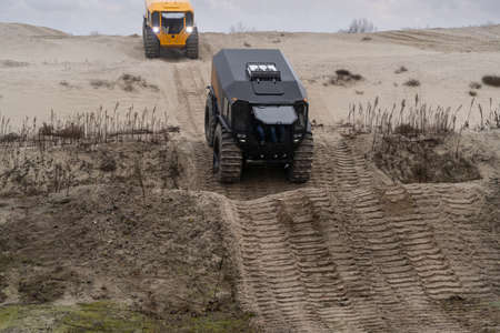 Two off-road vehicles driving in a sandy area Stock fotó