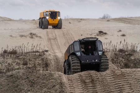 All-terrain vehicles driving through a sandy landscape Stockfoto