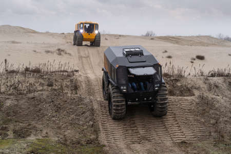 All-terrain vehicles driving through a sandy hilly landscape