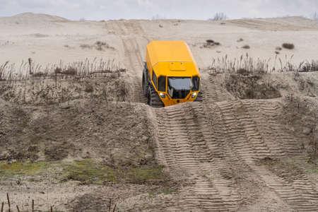 Yellow all-terrain vehicle touring through sandy hills