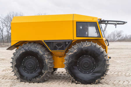 Ultimate all-terrain vehicle with huge big tires and strong yellow metal body Stock fotó