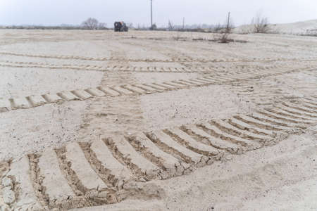Big tire marks in the sand and an off-roader in the distance