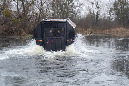 All-terrain vehicle with passengers crossing an icy river Stock fotó