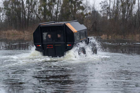 Amphibious off-road vehicle coming out of the river