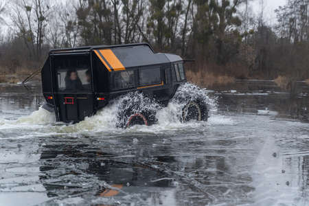 Off-road vehicle with passengers crossing an icy river