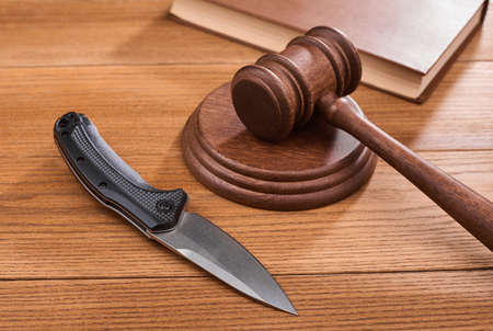 A folding knife, a judge s gavel and a book on wooden table Stock fotó