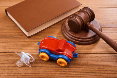 A pacifier, a car toy, a judge s gavel and a book on wooden table Stock fotó