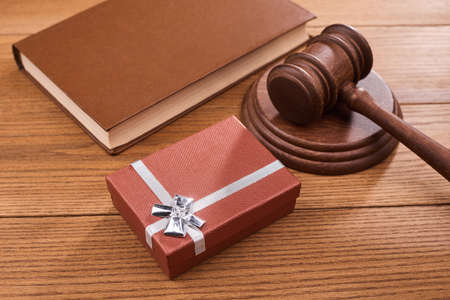 A gift box, a judge s gavel and a book on wooden table