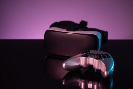 Joystick and VR headset on dark violet background